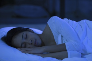 Woman sleeping better during the daytime in a dark bedroom